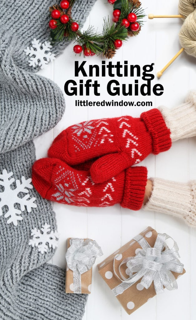 Hands in knitted mittens with grey scarf, snowflakes and gift boxes on white wooden table and the words knitting gift guide