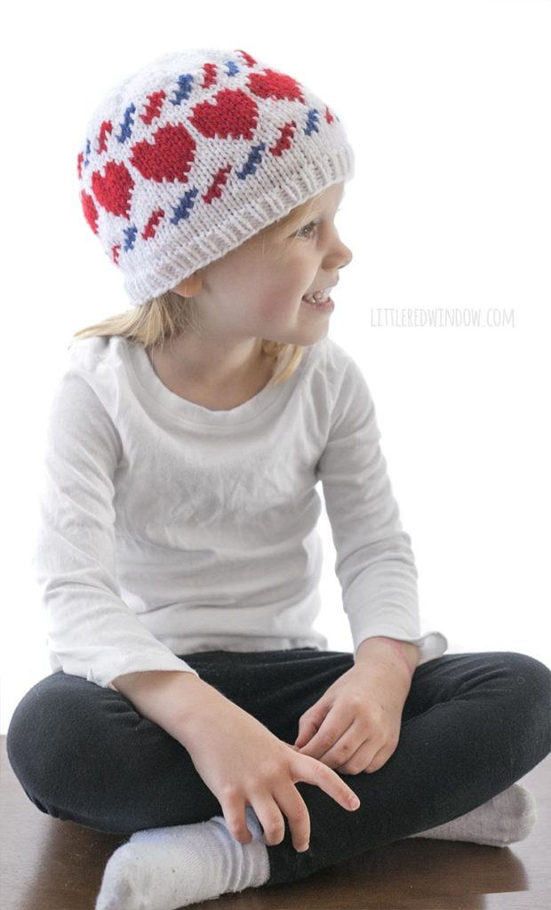 little girl sitting cross legged and wearing a white knit hat with red hearts and blue and red airmail stripes