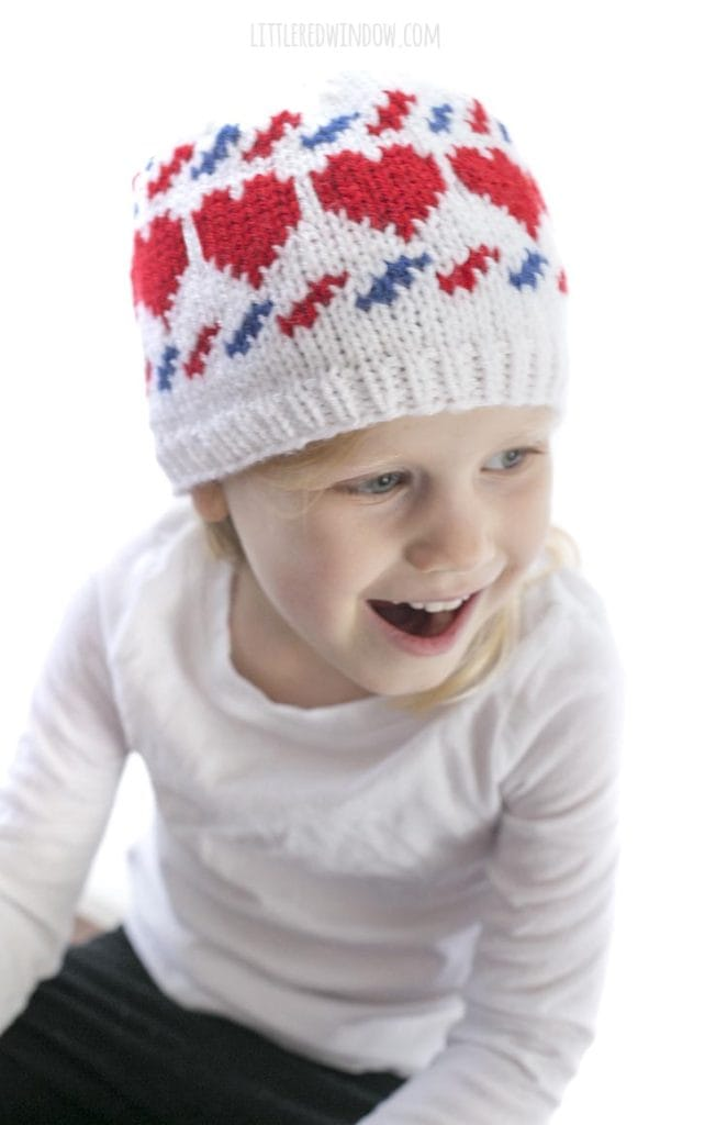 little girl laughing and wearing a white knit hat with red hearts and blue and red airmail stripes