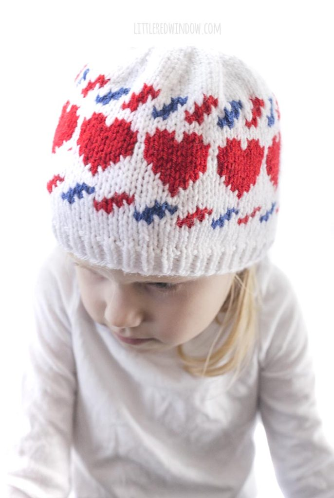 closeup of little girl and wearing a white knit hat with red hearts and blue and red airmail stripes