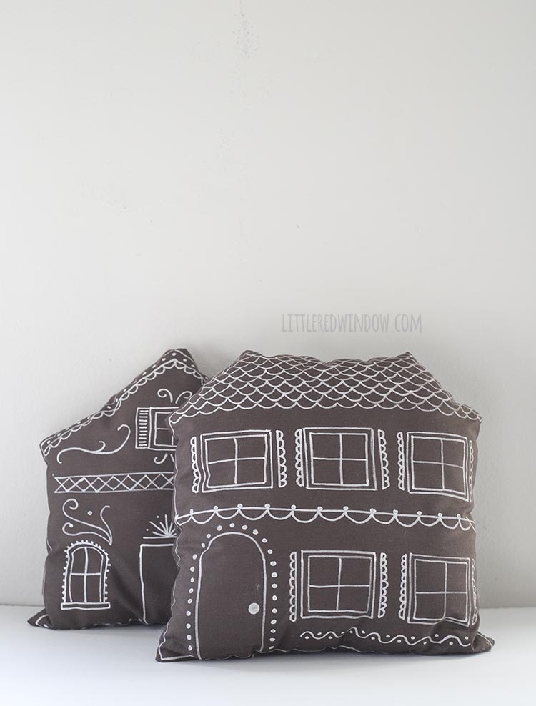 two brown pillows decorated like gingerbread houses leaning on a wall