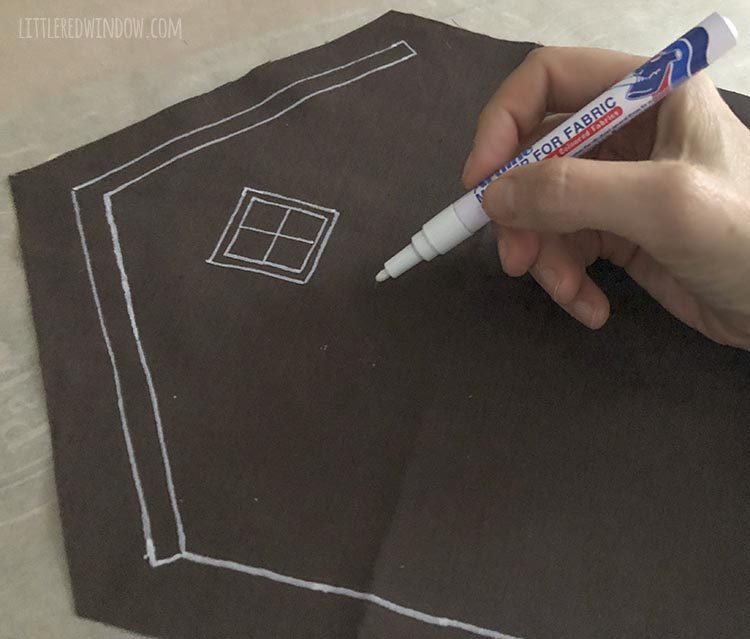 a hand holding a white pen drawing frosting decorations on a brown fabric gingerbread house shape