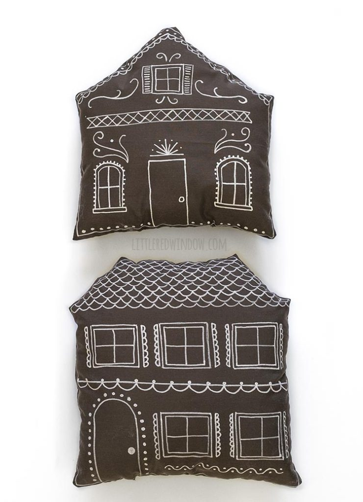 two brown pillows shaped and decorated like gingerbread houses on a white background