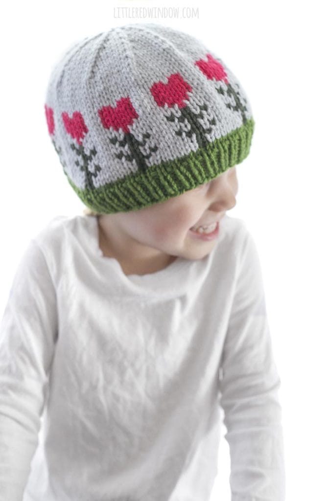 little girl in white shirt wearing light blue knit hat with pink heart shaped flowers on it