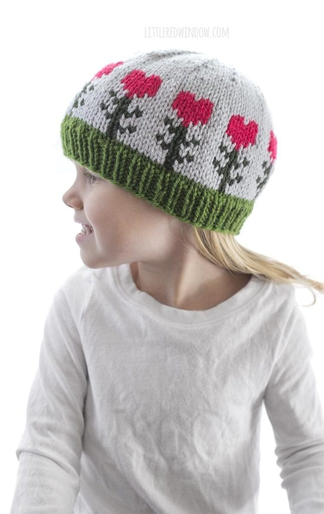 little girl in white shirt wearing light blue knit hat with pink heart shaped flowers on it looking off to the left