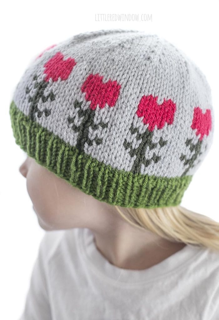 closeup of light blue knit baby hat with heart shaped flowers on it