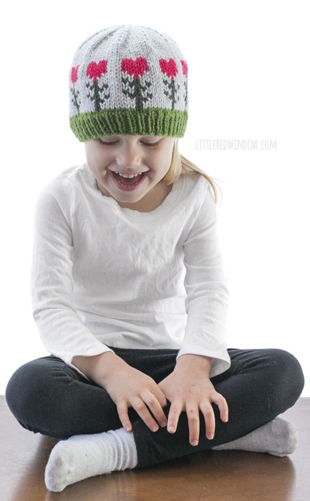 little girl in white shirt wearing light blue knit hat with pink heart shaped flowers on it looking down