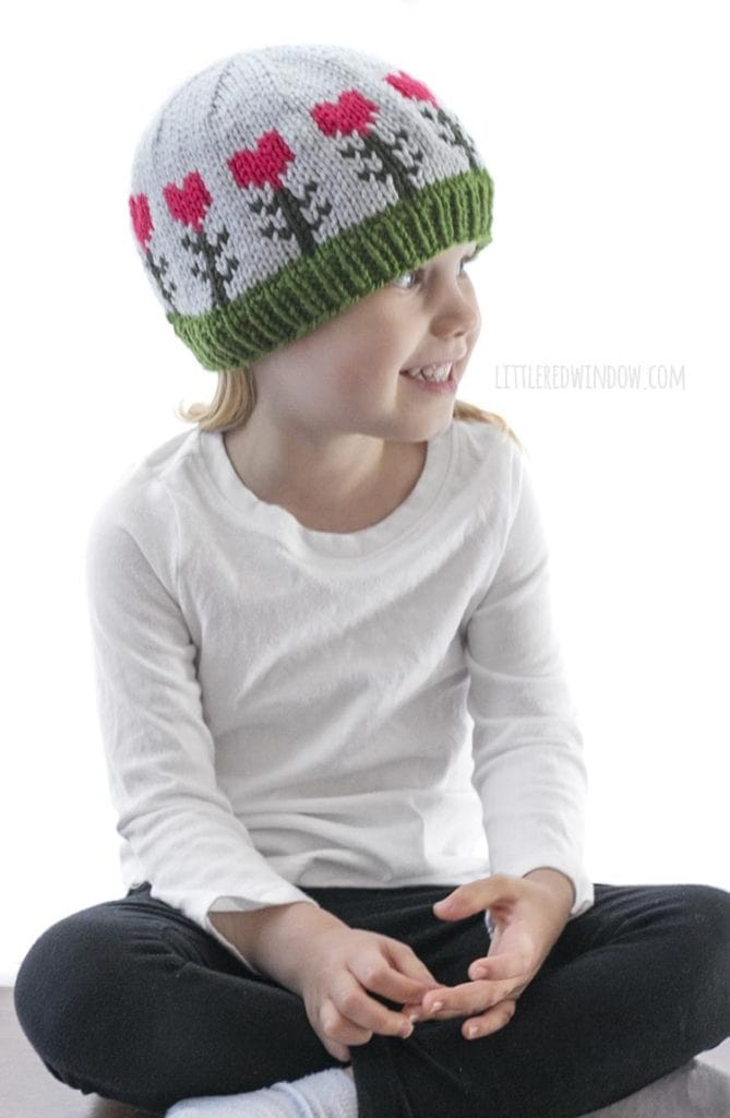 little girl in white shirt wearing light blue knit hat with pink heart shaped flowers on it looking off to the right