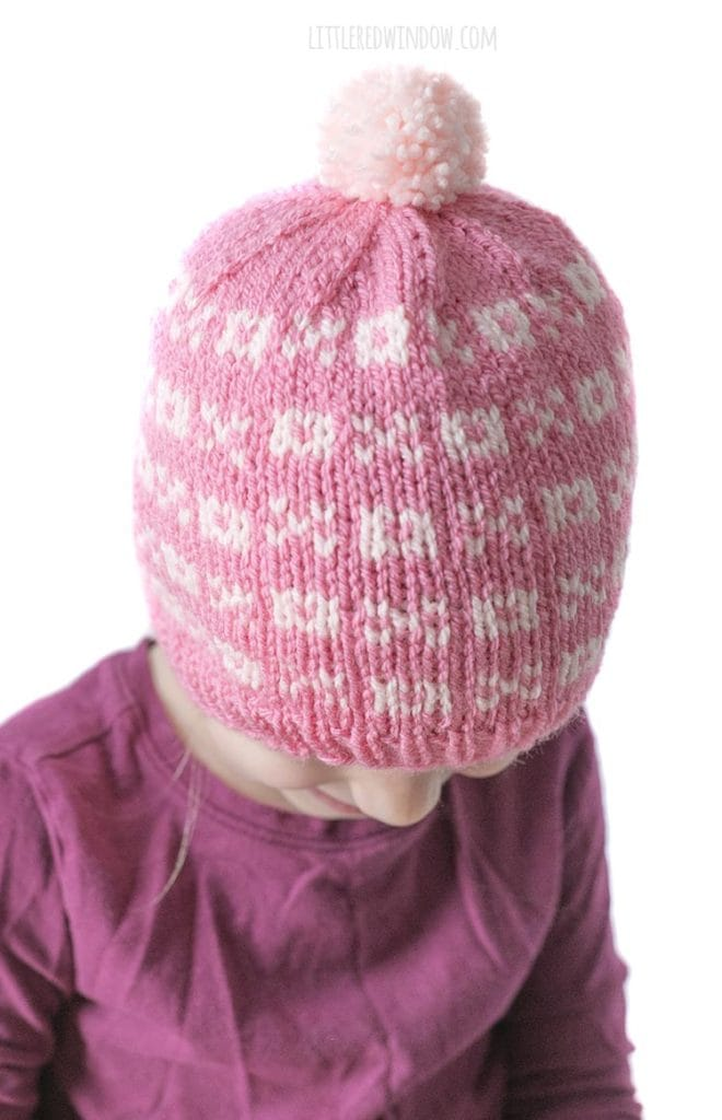 closeup of pink knit hat with light pink xs and os and a light pink pom pom