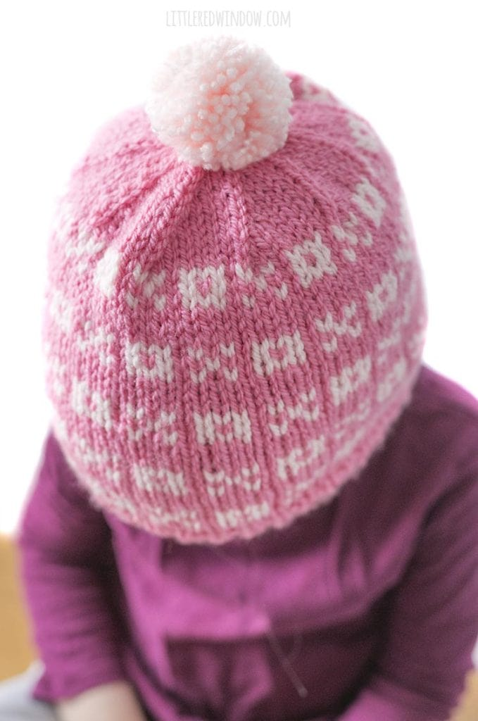 view of the top of the pink knit hat with xo pattern on it