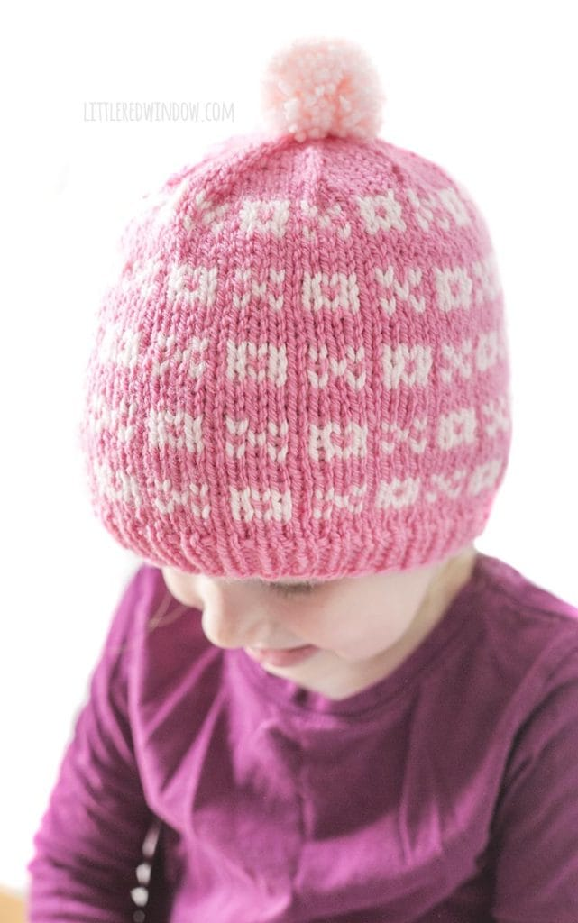 little girl in purple shirt wearing a light pink knit hat with alternating pattern of xs and os