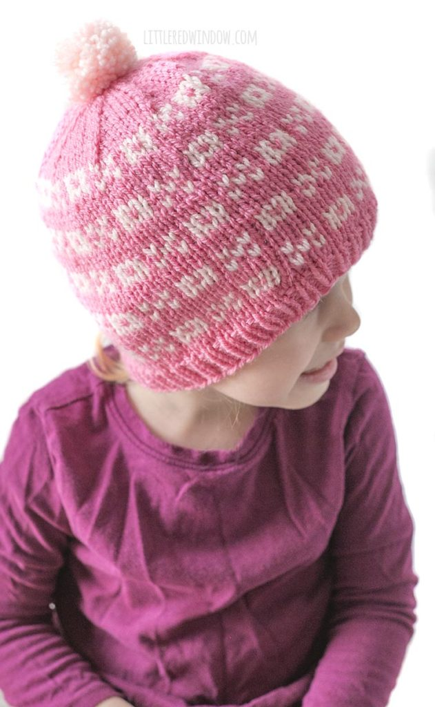little girl in purple shirt wearing a light pink knit hat with alternating pattern of xs and os looking off to the right