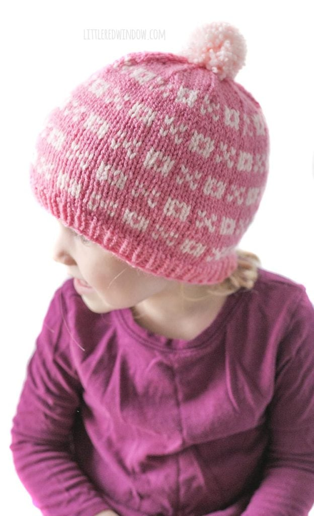 little girl in purple shirt wearing a light pink knit hat with alternating pattern of xs and os looking off to the left
