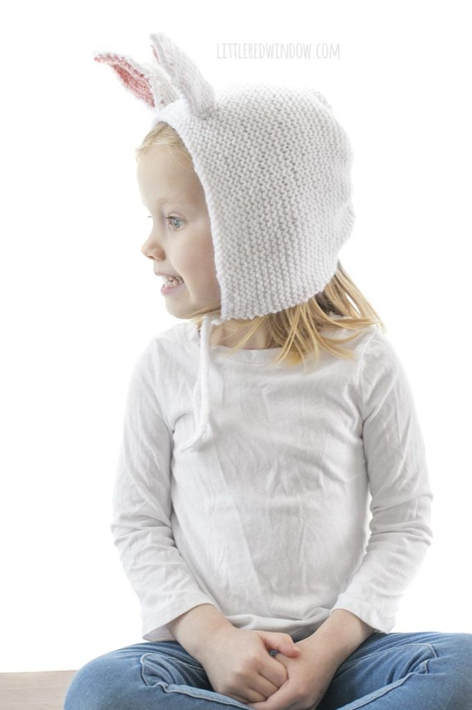 little girl wearing white knit bonnet with bunny ears and looking off to the left