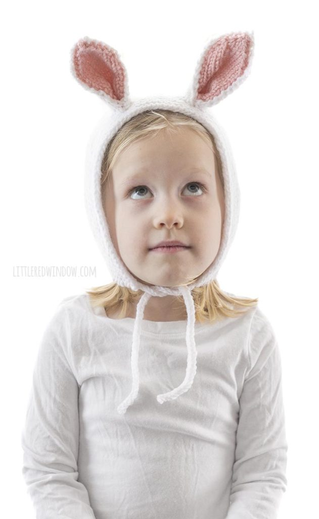little girl wearing white knit bonnet with bunny ears and looking up at the ceiling