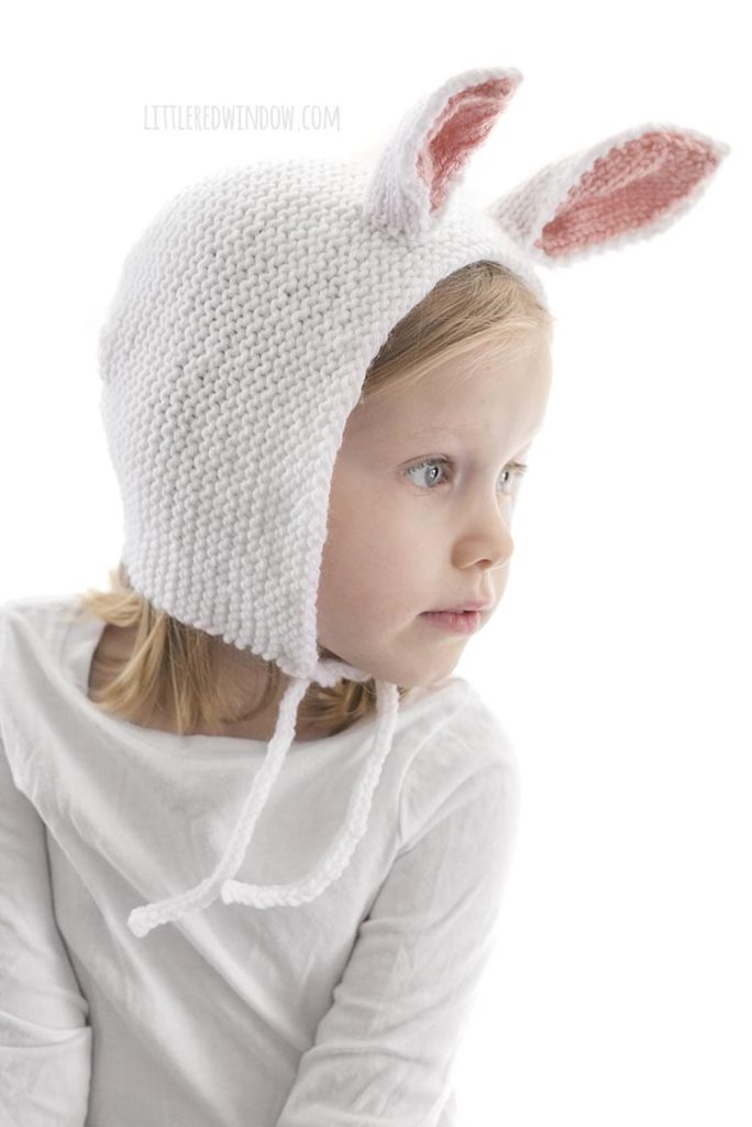 little girl wearing white knit bonnet with bunny ears and looking off to the right
