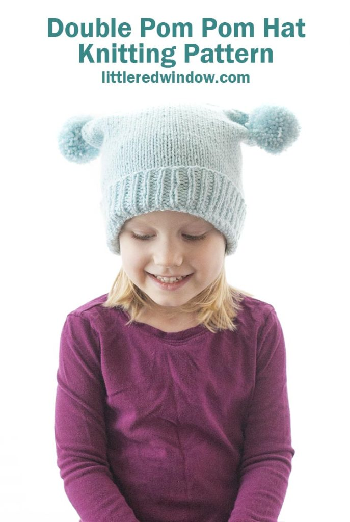 This cute double pom pom hat knitting pattern is a cute twist on a regular baby beanie and it's super easy to knit for your baby or toddler!