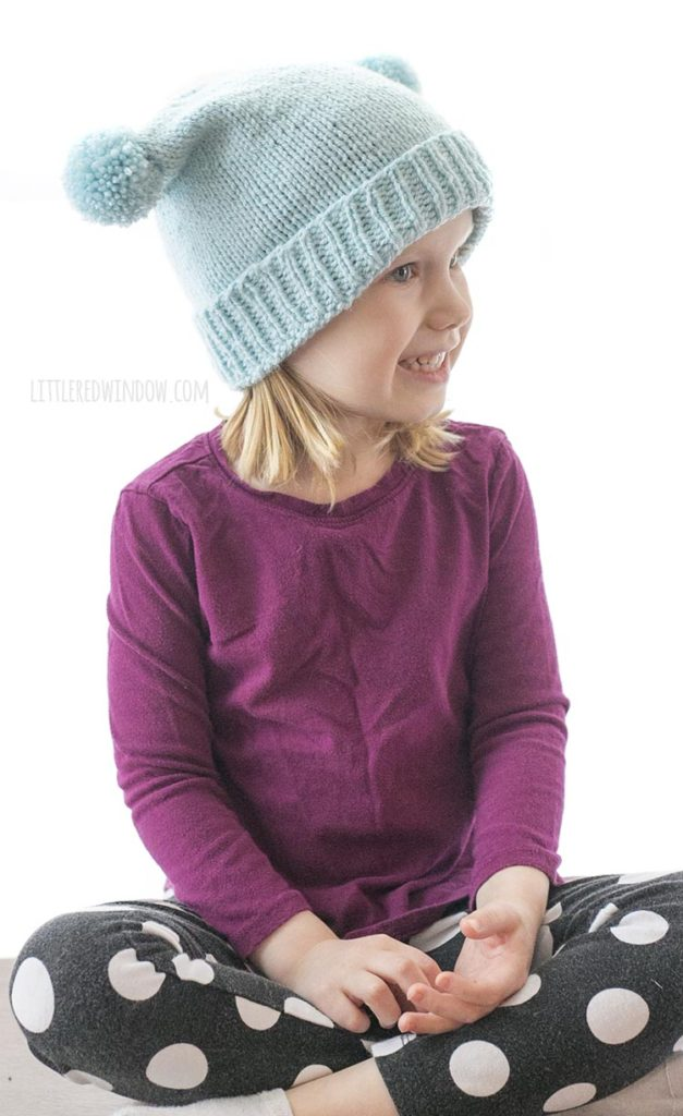 little girl wearing light blue hat with folded brim and two pom poms on the sides