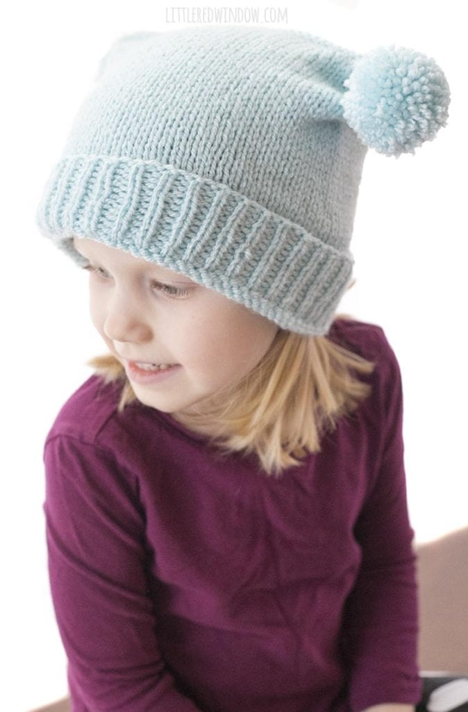 view from above of little blond girl in purple shirt wearing light blue knit hat with folded brim and two pom poms on top