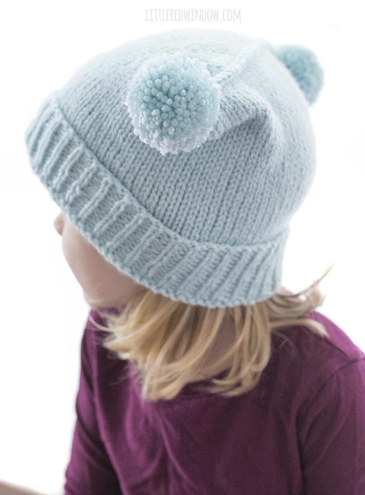 view of double pom pom hat knitting pattern from the back and above to show the three needle bind off across the top of the hat