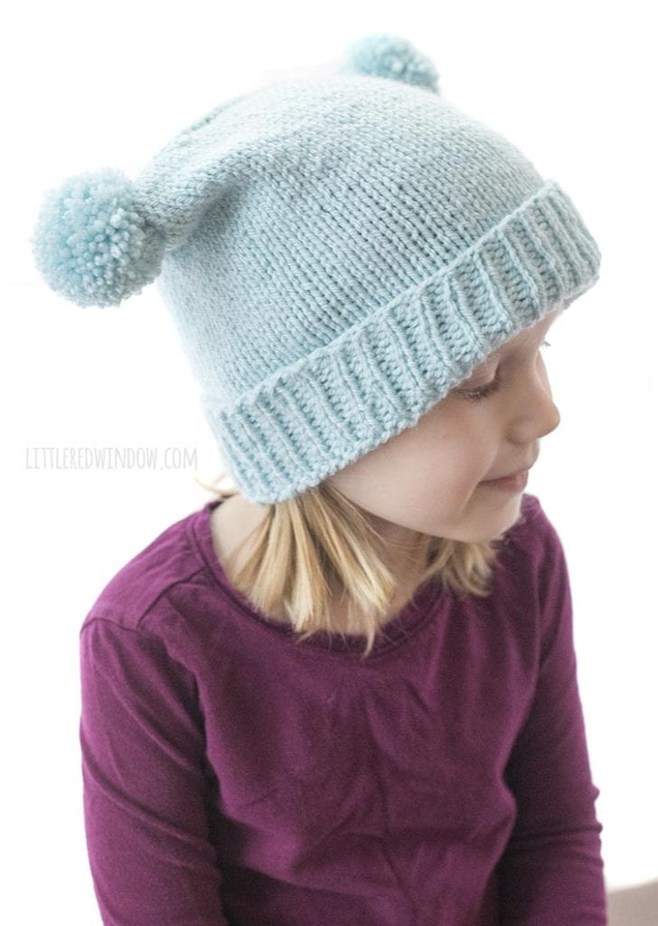 side view of double pom pom hat knitting pattern ona little girl in a purple shirt looking off to the right