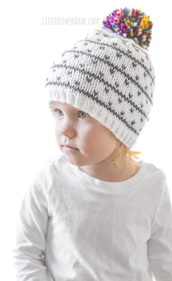 little girl wearing white knit hat with gray stripes and dots and a multicolored pom pom on top