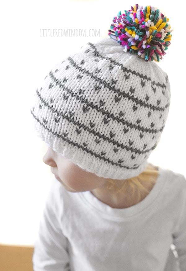 closeup of white and gray knit hat with multicolored pom pom on top