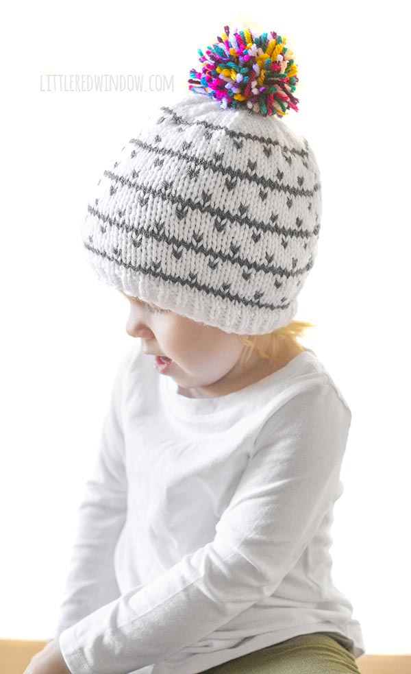 little girl in white shirt wearing gray and white knit hat with multicolored pom pom on top looking down to the left