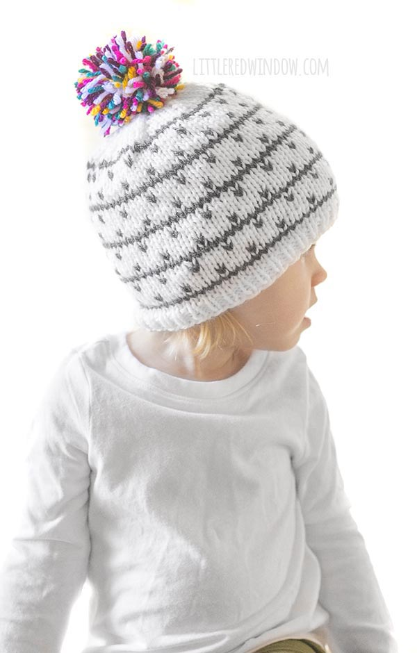 little girl in white shirt wearing gray and white knit hat with multicolored pom pom on top looking off to the right