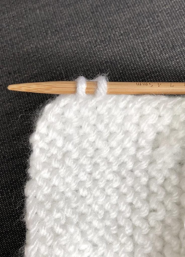 corner of garter stitch with one knitting needle picking up two stitches
