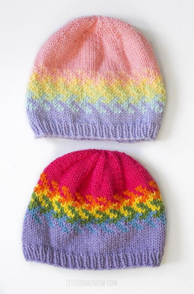 overhead view of two versions of the arrow fade rainbow fades hats knitting pattern one in pastel rainbow colors and one in bright rainbow colors