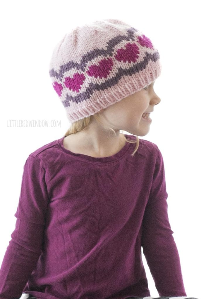 little girl wearing pink and purple knit hat with hearts and scallops pattern looking off to the right