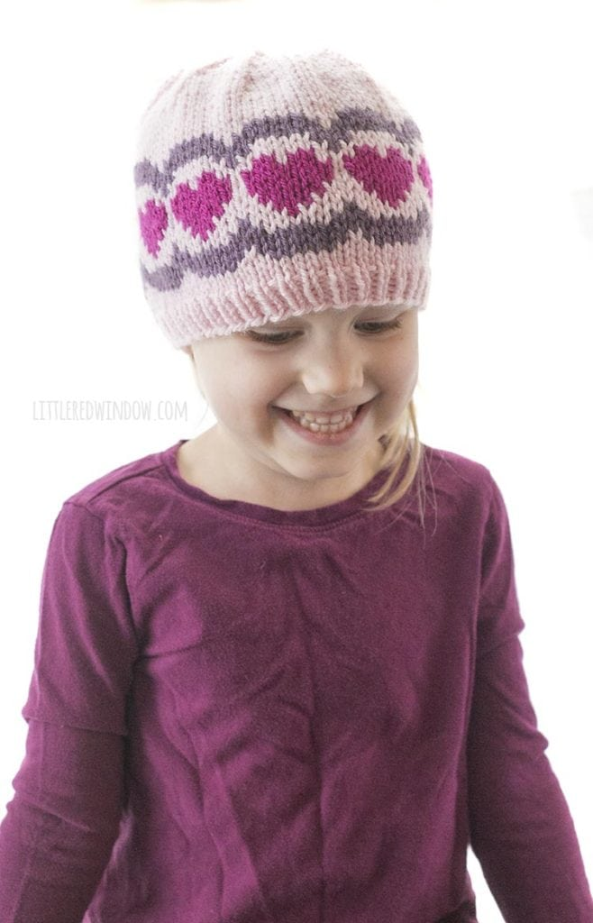 little girl smiling and wearing a pink and purple knit hat with hearts and scallops on it