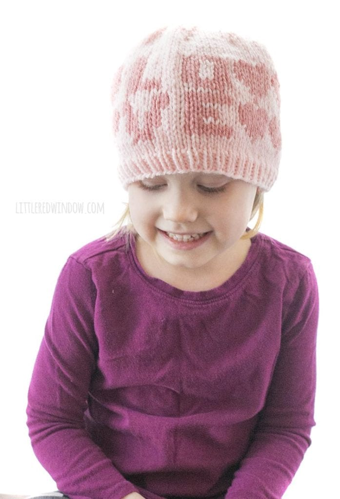 little girl in purple shirt wearing light pink hat with the word love on the front