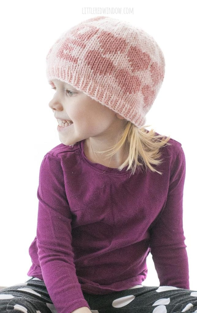 little girl in a purple shirt looking off to the left and wearing a light pink knit hat with the word LOVE and hearts around the sides