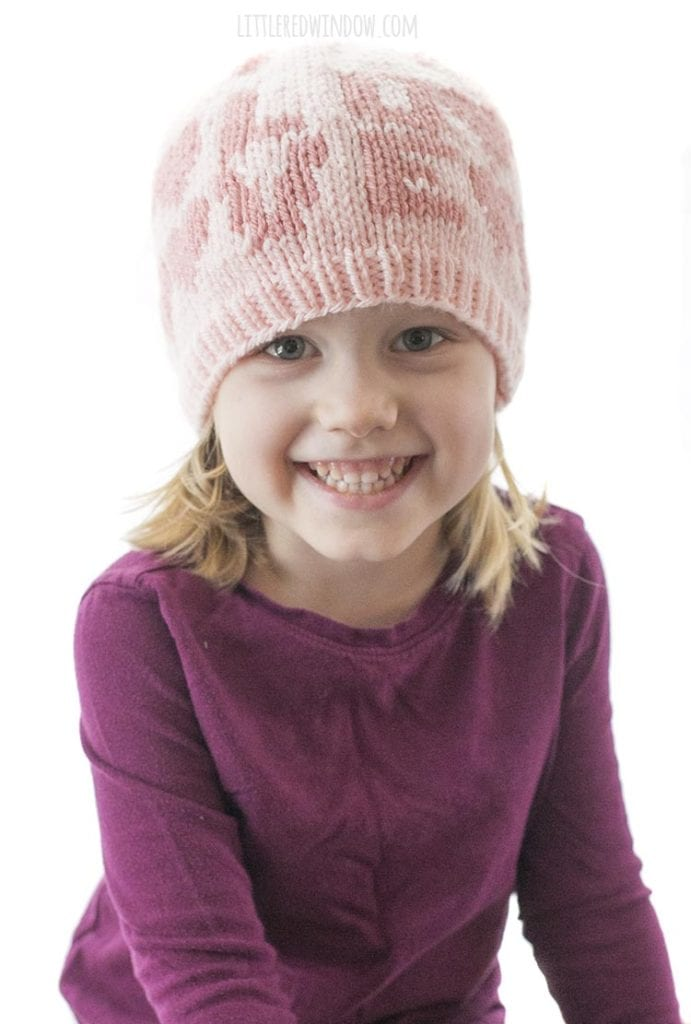 little girl smiling and wearing a light pink hat with the word LOVE on the front and hearts around the side