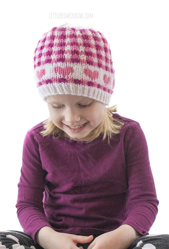 little girl in purple shirt wearing hat with pink hearts and pink gingham plaid