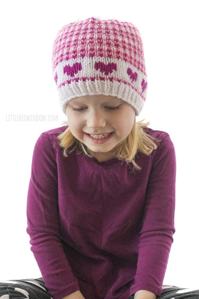 little girl in purple shirt wearing hat with pink hearts and small scale plaid looking down