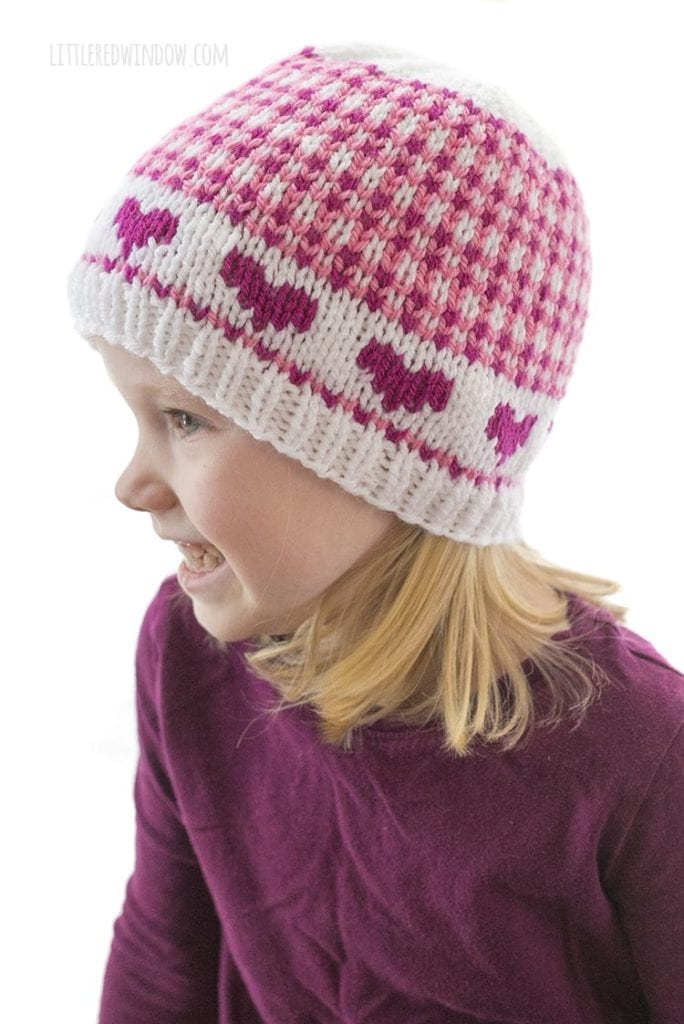 little girl in purple shirt wearing hat with pink hearts and small scale plaid looking off to the left