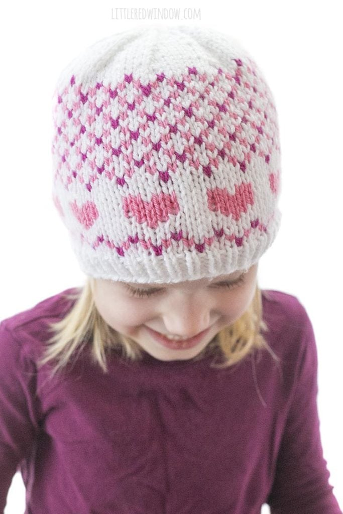 little girl in purple shirt wearing hat with pink hearts and small pink and white diagonal plaid looking down