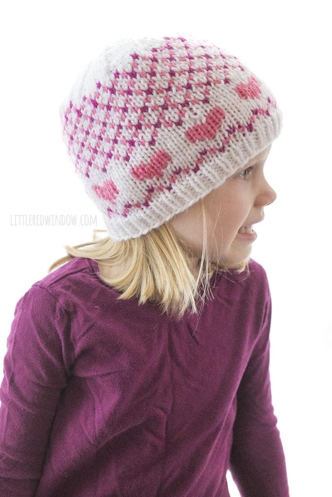 little girl in purple shirt wearing hat with pink hearts and small pink and white diagonal plaid looking off to the right