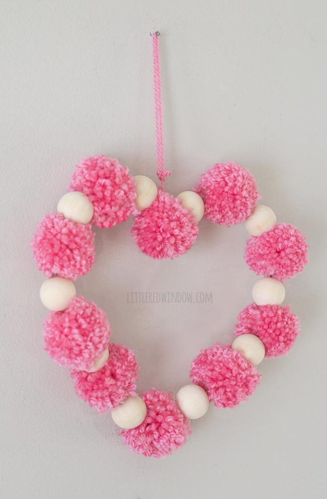 left angle view of heart shape made of pink pom poms and wood beads