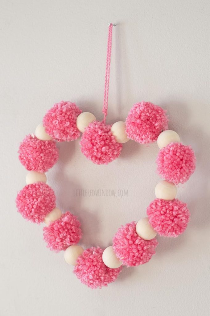 right angle view of heart shape made of pink pom poms and wood beads