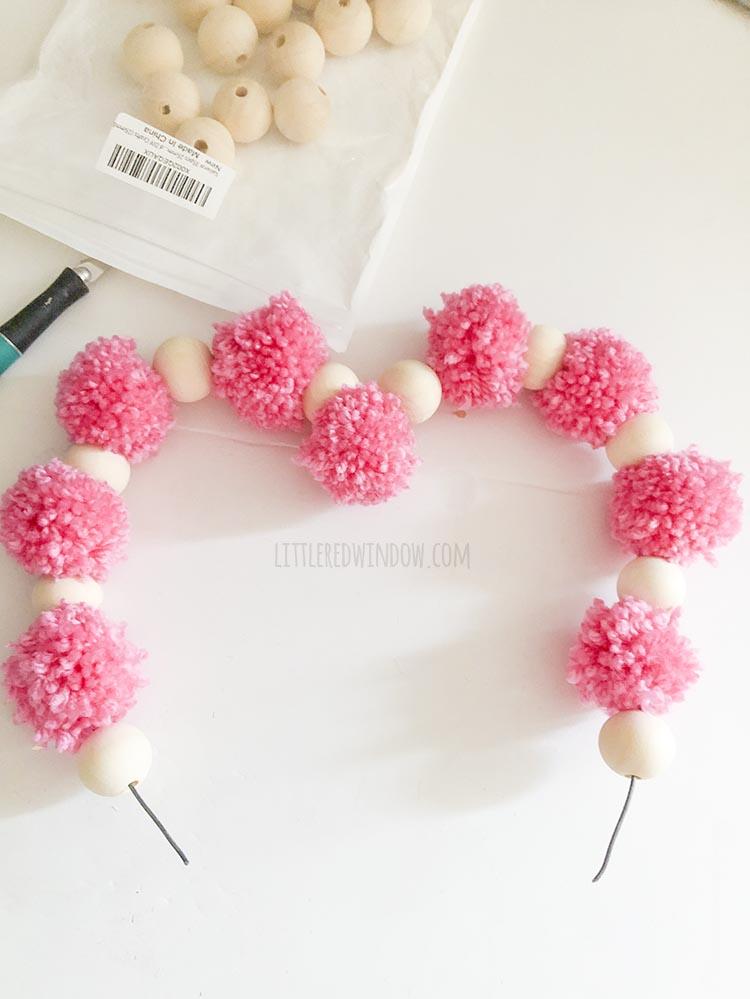 pom pom and wood bead heart shape halfway complete