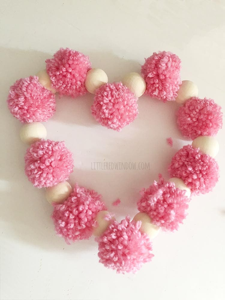 overhead view of finished valentine pom pom heart craft on a white background