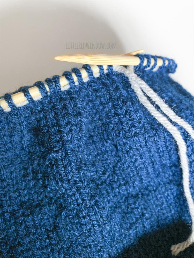 closeup of a blue knit hat being knit with a lifeline inserted through the live knitting stitches