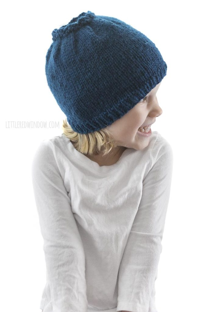 little girl in white shirt looking off to the right and wearing a blue knit hat that looks like a blueberry