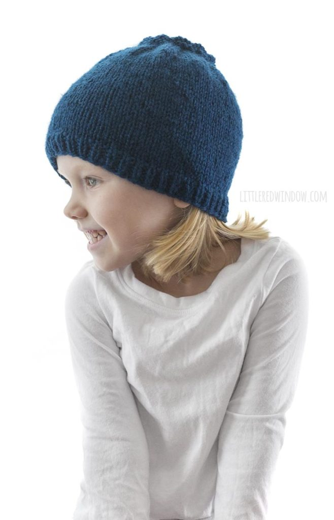 little girl in white shirt looking off to the left and wearing a blue knit hat that looks like a blueberry