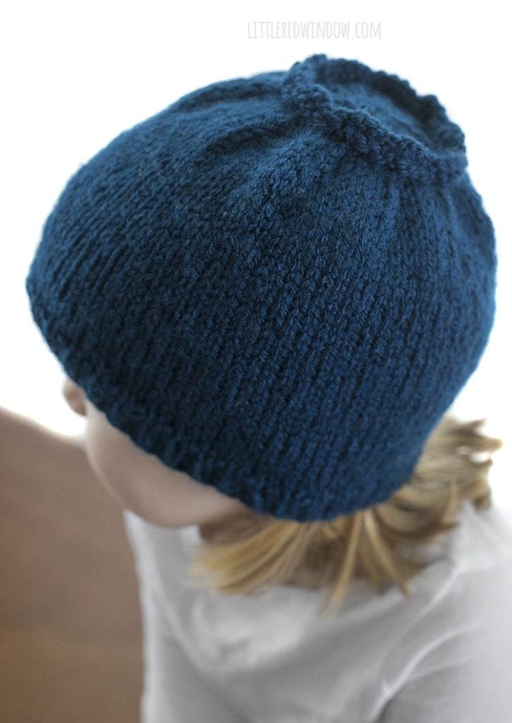Over the shoulder top view of little girl in white shirt wearing a blue knit hat that looks like a blueberry