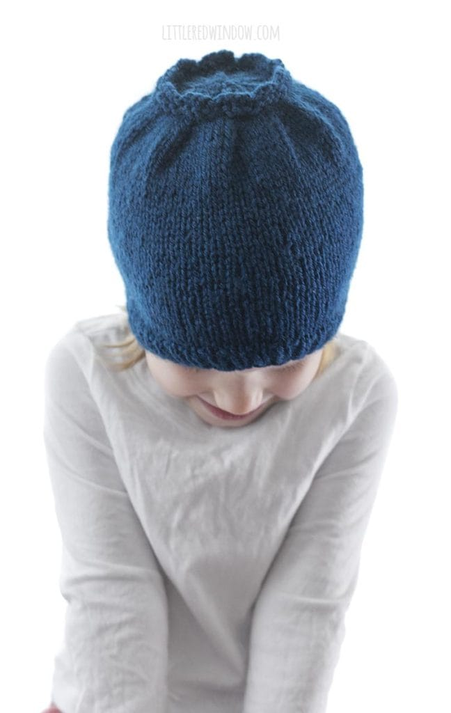 little girl in white shirt looking down and wearing a blue knit hat that looks like a blueberry